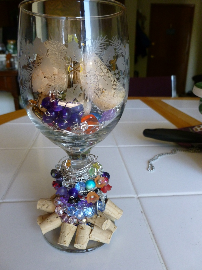 Around and inside this wine glass are 80 wine glass charms - all different and unique and 4 wine cork key chains.